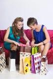2 девушки рассматривают и показывают приобретения одина другого Стоковое Изображение RF