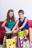 2 девушки рассматривают и показывают приобретения одина другого Стоковые Фото