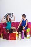 2 девушки рассматривают и показывают приобретения одина другого Стоковое Изображение