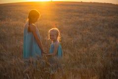2 девушки ребенка на поле захода солнца Стоковые Изображения RF