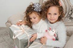 2 девушки ребенка с подарками на тренере на времени рождества Стоковые Изображения