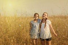 2 девушки ребенк имея потеху на поле Стоковая Фотография RF