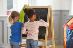 2 девушки рисуя изображение на классн классном дома Стоковая Фотография