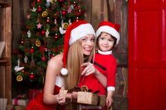 2 девушки Санты украшая рождественскую елку имея потеху Интерьер Нового Года Атмосфера Xmas, семья празднуя праздники Стоковые Изображения RF