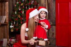 2 девушки Санты украшая рождественскую елку имея потеху Интерьер Нового Года Атмосфера Xmas, семья празднуя праздники Стоковая Фотография