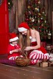 2 девушки Санты украшая рождественскую елку ново Стоковое Фото