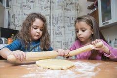 2 девушки свертывая вне тесто на кухонном столе Стоковая Фотография RF