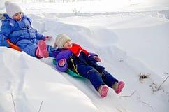 2 девушки свертывая вниз холм в снеге Стоковая Фотография RF