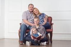3 девушки семьи кресла камеры смотрящ сидеть re портрета мати померанцовый их там Стоковое Фото