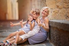 3 девушки семьи кресла камеры смотрящ сидеть re портрета мати померанцовый их там Стоковое фото RF