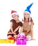 2 девушки сестры в крышках Санта Клауса около Стоковые Изображения