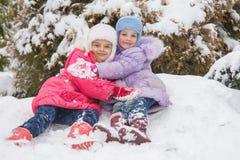2 девушки сидят в снеге сугроба и обнимают один другого Стоковое Изображение RF