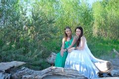 2 девушки сидят на журнале морем Стоковое Фото