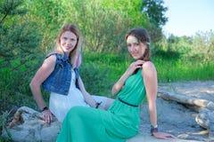 2 девушки сидят на журнале морем Стоковые Изображения RF