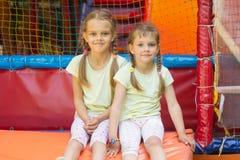 2 девушки сидят на мягком выходе от игровой комнаты Стоковая Фотография