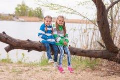 2 девушки сидят на упаденном дереве на речном береге Стоковое Изображение