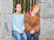 2 девушки сидя в каменном окне Стоковое Фото