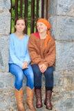 2 девушки сидя в каменном окне Стоковые Фото