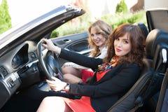 2 девушки сидя в обратимом салоне Стоковое Изображение