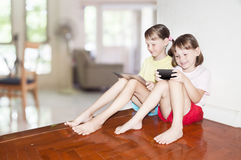 2 девушки сидя и играя Стоковые Изображения