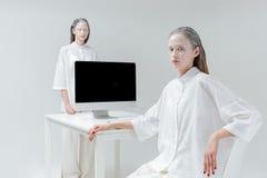 2 девушки сидя и стоя около стола с компьютером Стоковые Фото