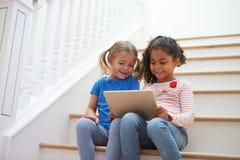 2 девушки сидя на лестнице используя таблетку цифров Стоковое фото RF