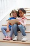 2 девушки сидя на лестнице используя таблетку цифров Стоковая Фотография RF
