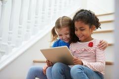 2 девушки сидя на лестнице используя таблетку цифров Стоковые Изображения RF