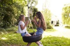 2 девушки сидя на качании играя хлопающ игра Стоковое Изображение