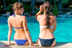 2 девушки сидя на краю бассейна Стоковая Фотография