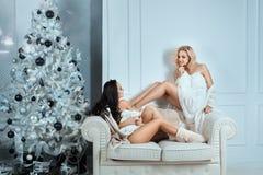 2 девушки сидя на кресле говоря дома Стоковое фото RF