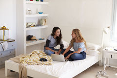 2 девушки сидя на кровати используя компьтер-книжку смотря один другого Стоковые Фото