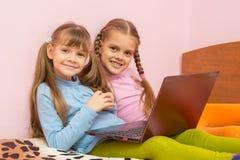 2 девушки сидя на кровати с компьтер-книжкой и потехой смотрят в рамку Стоковая Фотография