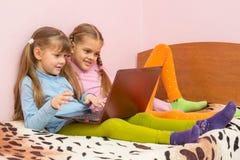2 девушки сидя на кровати с компьтер-книжкой Стоковые Изображения RF