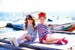 2 девушки сидя на доке Стоковые Изображения RF