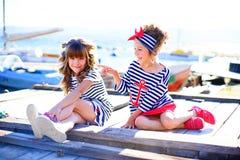 2 девушки сидя на доке Стоковая Фотография RF