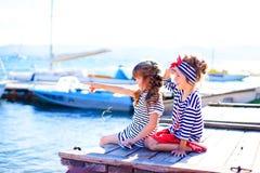 2 девушки сидя на доке Стоковые Фото