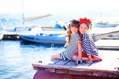2 девушки сидя на доке Стоковое Фото