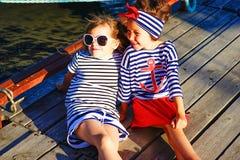 2 девушки сидя на доке Стоковое Изображение