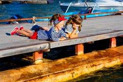 2 девушки сидя на доке Стоковая Фотография