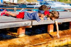 2 девушки сидя на доке Стоковые Фотографии RF