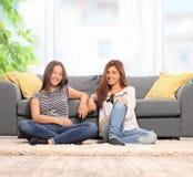 2 девушки сидя на поле перед креслом Стоковое Изображение RF