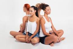 4 девушки сидя на поле Стоковые Фотографии RF