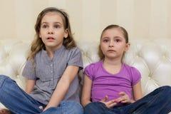2 девушки сидя на софе и смотря TV умышленно Стоковая Фотография