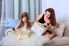 2 девушки сидя на софе с подарками рождества Стоковые Фотографии RF