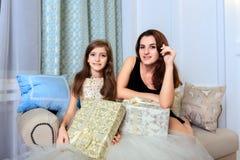 2 девушки сидя на софе с подарками рождества Стоковая Фотография