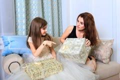 2 девушки сидя на софе с подарками рождества Стоковое фото RF