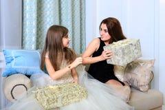 2 девушки сидя на софе с подарками рождества Стоковые Фото
