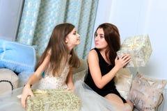 2 девушки сидя на софе с подарками рождества Стоковое Изображение RF
