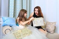 2 девушки сидя на софе с подарками рождества Стоковые Изображения